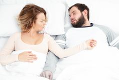 Couple in bed. Man snoring and woman can`t sleep. Snore noise. Couple in bed, men snoring and women can`t sleep Royalty Free Stock Image