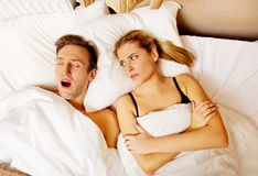Couple in bed,man snoring woman can't sleep Stock Image