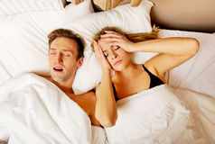 Couple in bed,man snoring woman can't sleep Royalty Free Stock Images
