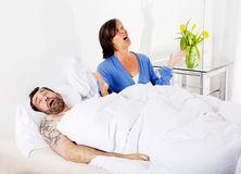 Couple in bed. Man is snoring and women is upset Royalty Free Stock Image