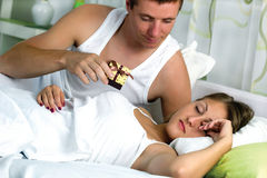 Couple in bed, man wants to surprise his wife with a gift Stock Image