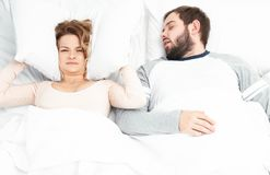 Man snoring and woman can`t sleep, covering ears with pillow for snore noise. Couple in bed, men snoring and women can`t sleep, covering ears with pillow for stock photography