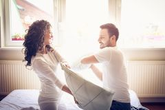Fight in bed with pillow. Couple on bed playing with pillow.  Funny morning in bedroom Stock Photos