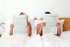 Couple in bed reading a newspaper. Information