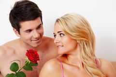 Couple in bed with rose. proposal. A romentic couple in bed with rose. marry the men stock photos