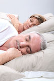 Couple in bed sleeping. Mature couple in bed sleeping royalty free stock photos