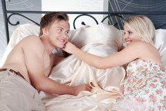 Couple in bed and smile at each other Stock Images
