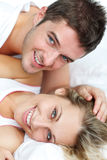 Couple in bed smiling Royalty Free Stock Photos