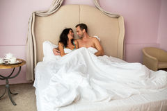Couple in bed smiling. Royalty Free Stock Image