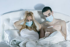 Couple in bed suffering common cold. Couple in bed suffering from common cold Royalty Free Stock Photography