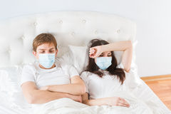Couple in bed suffering common cold. Couple in bed suffering from common cold Stock Images