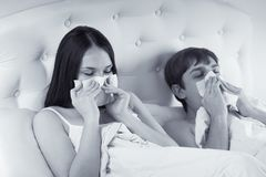 Couple in bed suffering common cold. A couple in bed suffering common cold Stock Photos