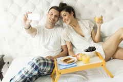 Couple in bed taking selfie Stock Image