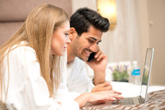 Couple in Bed using laptop and Husband talking on Phone Stock Photography