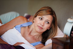 Couple In Bed With Wife Suffering From Insomnia. Looking At Alarm Clock royalty free stock photos