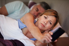 Couple In Bed With Wife Suffering From Insomnia. Looking At Mobile Phone stock photography