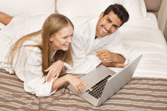 Couple in bed working on laptop Stock Photos