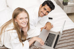 Couple in bed working on laptop Royalty Free Stock Photos