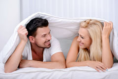Couple in bed. Young love couple in bed, under the covers, smiling into the camera in her bedroom Royalty Free Stock Photography