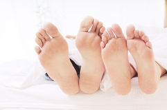 Couple in the bedroom. Foots of two people in the bedroom, sleeping and relax on the white background Royalty Free Stock Images