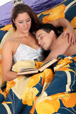 Couple bedroom book sleeping. Young attractive woman  reading book in bed in bedroom, husband sleeping.  Studio Royalty Free Stock Photos