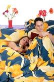 Couple bedroom book sleeping. Young handsome man  reading book in bed in bedroom, wife sleeping.  Studio Stock Images