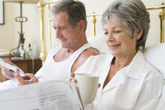 Couple in bedroom with coffee and newspapers Stock Photos