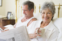Couple in bedroom with coffee and newspapers Royalty Free Stock Image