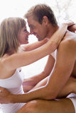 Couple in bedroom embracing and smiling Stock Image