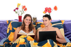 Couple, bedroom laptop book Stock Images