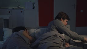 Couple in bedroom. overworked manager. Young man working at home at night. Boyfriend lying in bed using computer near sleeping girlfriend. Guy turn off light stock footage