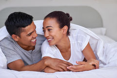 Couple bedroom. Romantic young affectionate married couple on bed under duvet at home Royalty Free Stock Photography