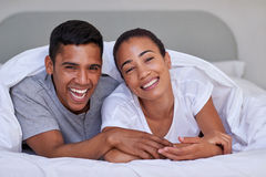 Couple bedroom. Romantic young affectionate married couple on bed under duvet at home Stock Photos