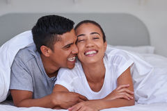 Couple bedroom. Romantic young affectionate married couple on bed under duvet at home Royalty Free Stock Photos