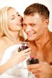 Couple in bedroom with wine Stock Images