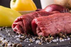 Couple of beef slices prepared for roulade with spice. Horizontal photo of two rolled beef slices. Meat is prepared for roulade and placed on black slate stone Stock Images