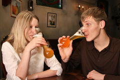 Couple with beer in bar. Couple drinking shaping beer in bar Stock Image