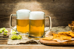 Couple beer mug with hop and chips on boards at linen cloth Royalty Free Stock Photos