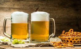 Couple beer mug with hop and pretzels on linen cloth Royalty Free Stock Photos