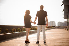 Couple from behind holding hands looking on city Stock Photos