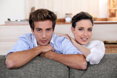Couple behind sofa Stock Images