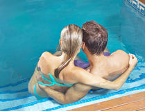 Couple from behind in swimming pool Royalty Free Stock Photos
