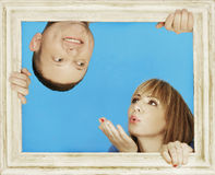 Couple Behind Wooden Frame on Sky Blue Background Stock Photos