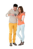 Couple being surprised by received message. Couple reading text message on smartphone Royalty Free Stock Images