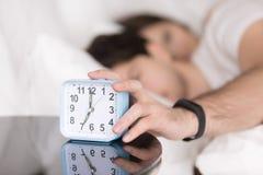 Couple being woken by alarm, man turning off ringing clock Royalty Free Stock Image