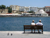 Couple on a bench. Couple sitting on a bench in Chania Greece Stock Image