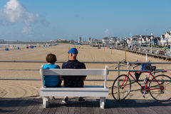 Couple on Bench on the Boardwalk. Avon-by-th-Sea, NJ USA -- Aug 4, 2016 Man and woman  relaxing on a bench on the boardwalk. Editorial Use Only Stock Photo