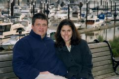 Couple on bench in front of marina. A husband and wife sit next to each other on a wooden bench in front of a boat marina stock photography