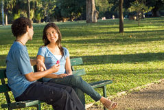 Couple on a Bench Looking at a Flower - Horiz Stock Photo