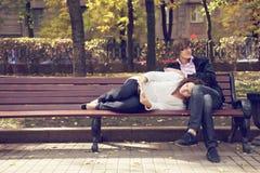Couple on bench reading book Stock Photos